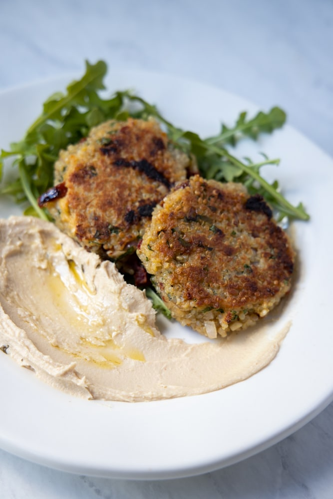 Sundried tomato and basil quinoa patties on a plate with hummus and arugula.