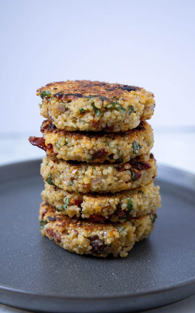 sundried tomato and basil quinoa patties stacked tall on a plate.