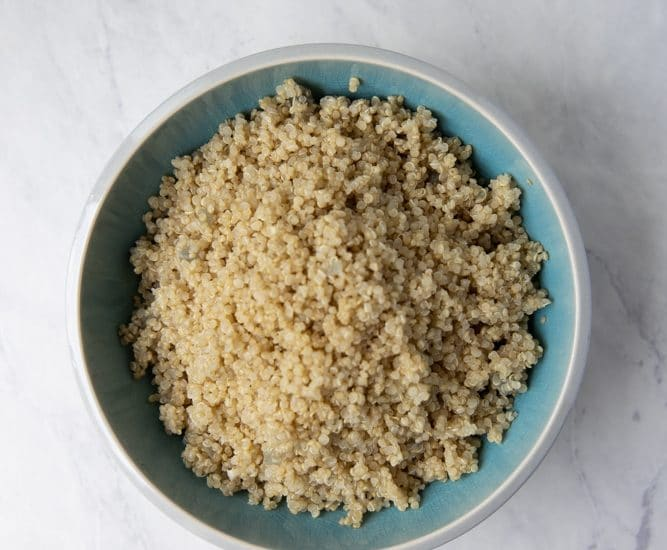 fluffy cooked quinoa piled in a bowl