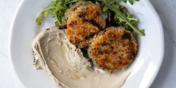 overhead photo of quinoa patties on a plate with hummus