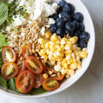 Tomatoes, corn, blueberries and barley in a bowl.