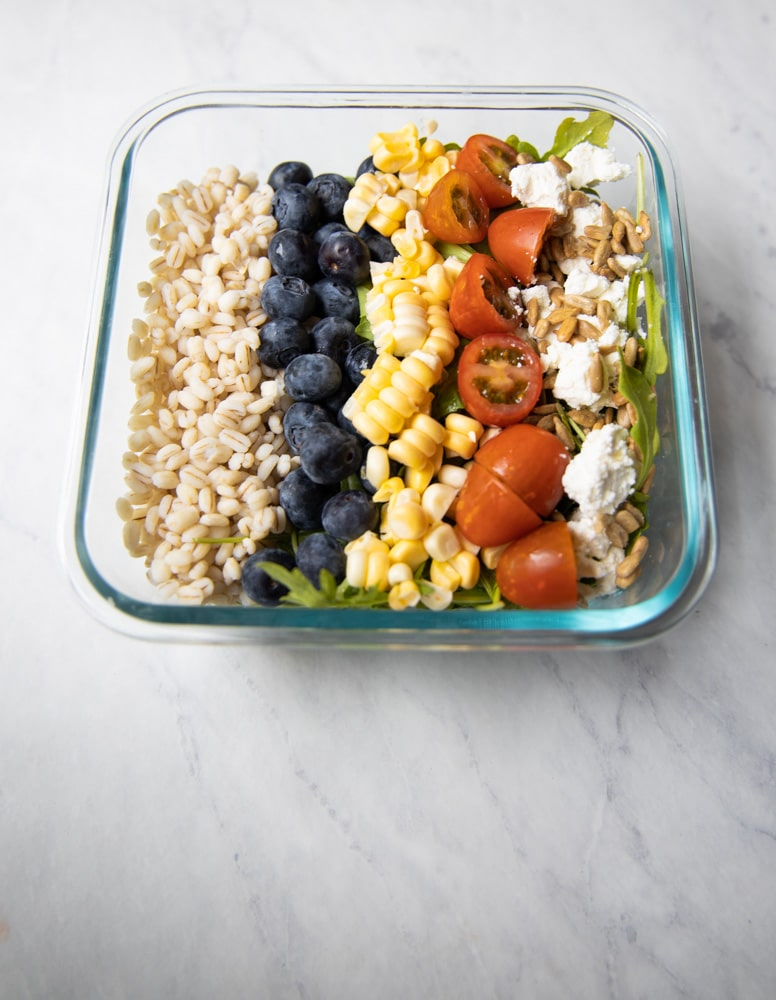 summer grain bowl with cherry tomatoes, corn and blueberries