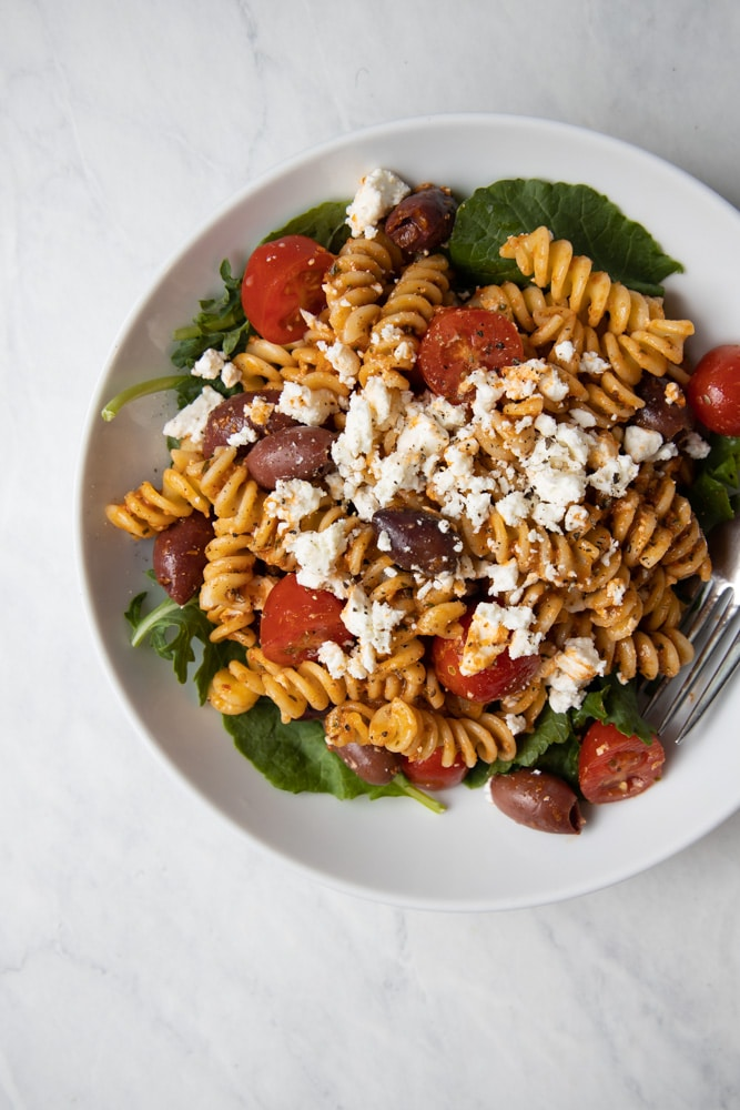 red pepper pasta salad in a bowl with kalamata olives, feta, cherry tomatoes and baby kale