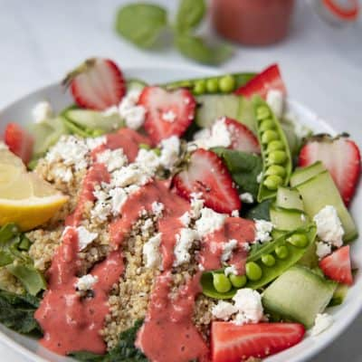 strawberry summer quinoa salad in a bowl with strawberry basil dressing drizzled on top
