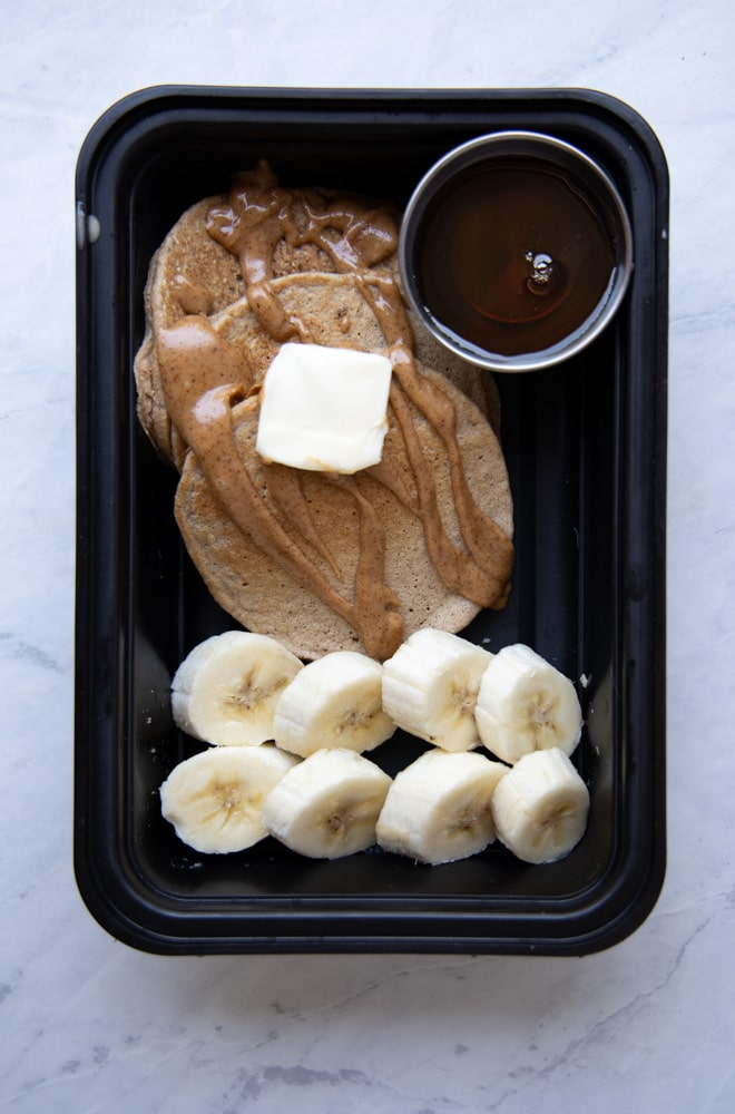 banana oat pancakes in a container with sliced bananas and maple syrup