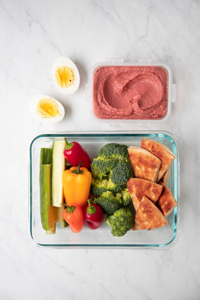 Tupperware with sliced veggies and pita bread with lemon beet hummus on the side