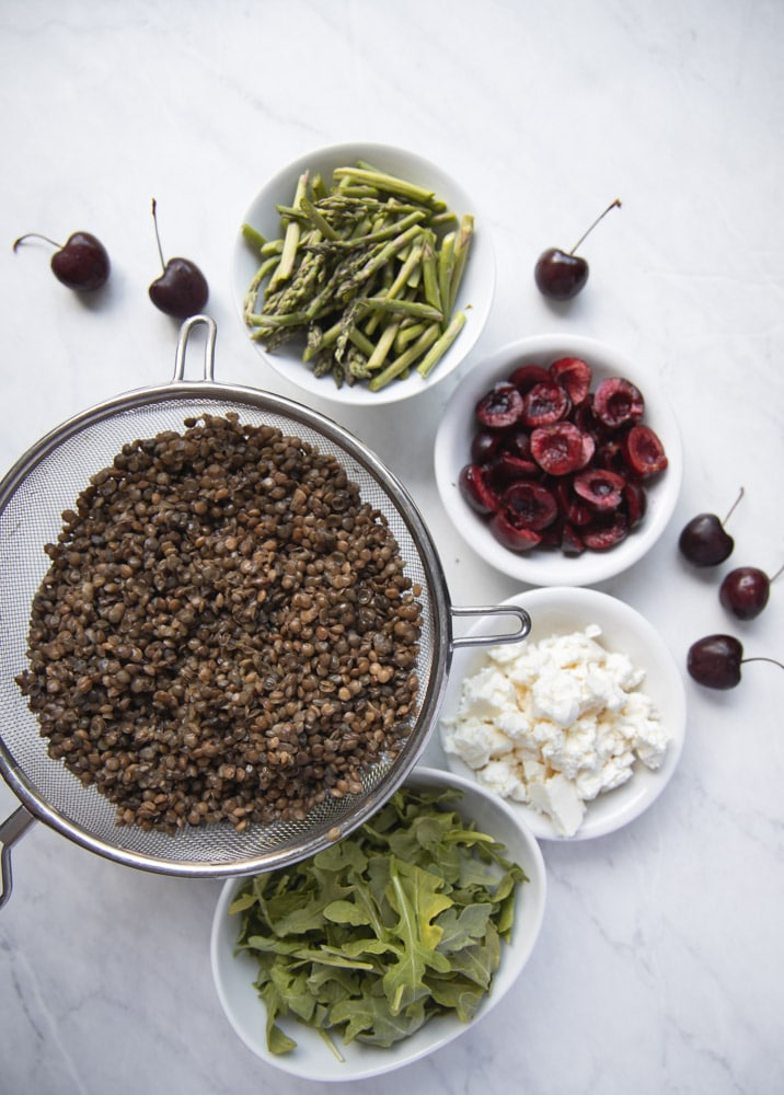 ingredients for cherry lentil salad in individual bowls
