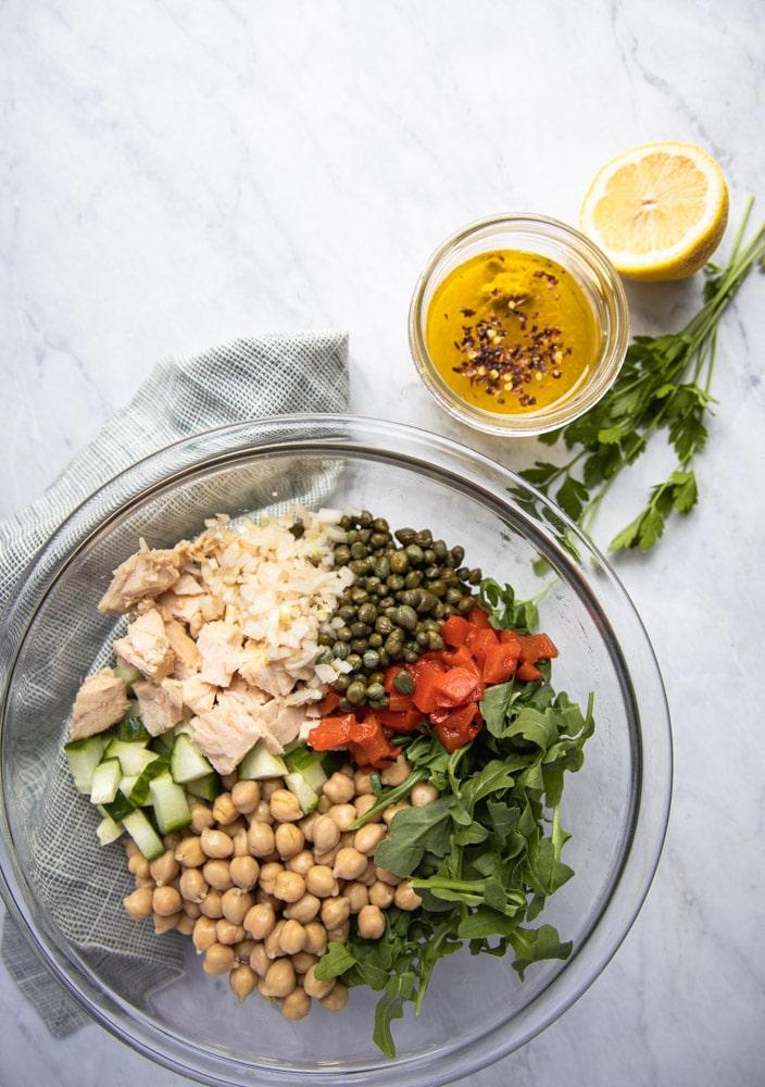 bowl full of ingredients for mediterranean tuna salad