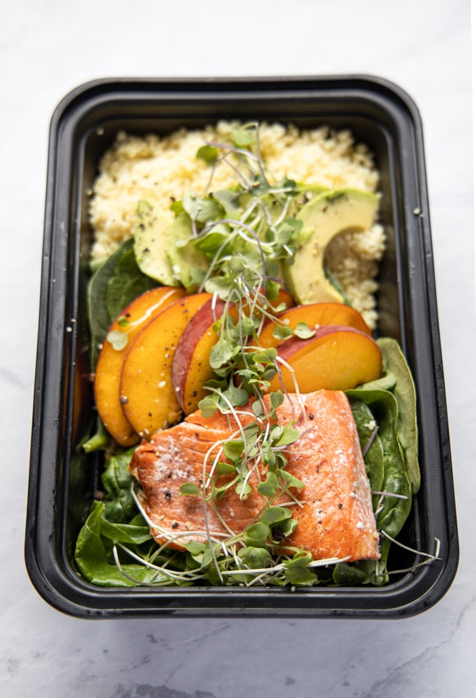 salmon peach bowl in a black meal prep container