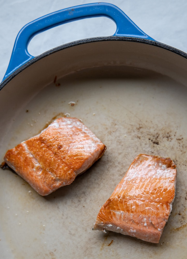 salmon filets being seared in a pan
