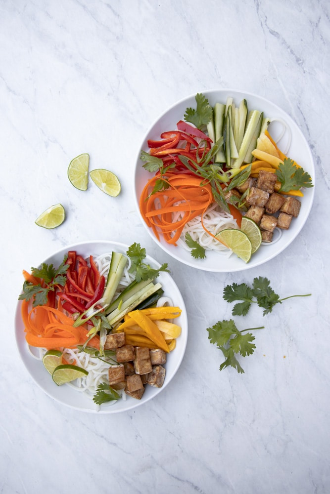 overhead photo of bowl of noodles with carrots, cucumber, mango, bell pepper and tofu