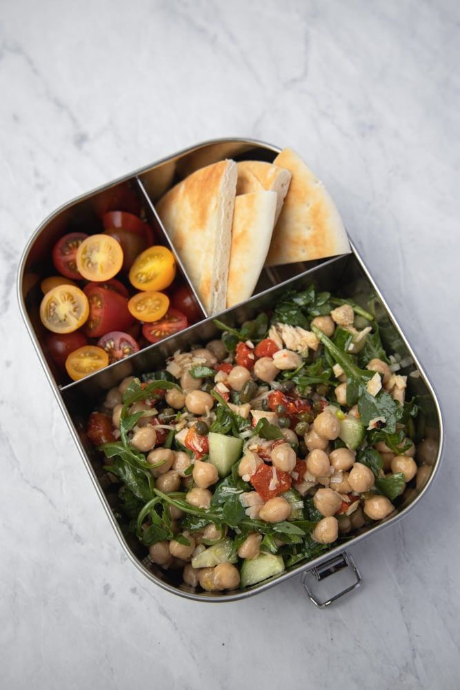 tuna salad in a meal prep container with pita triangles and sliced cherry tomatoes