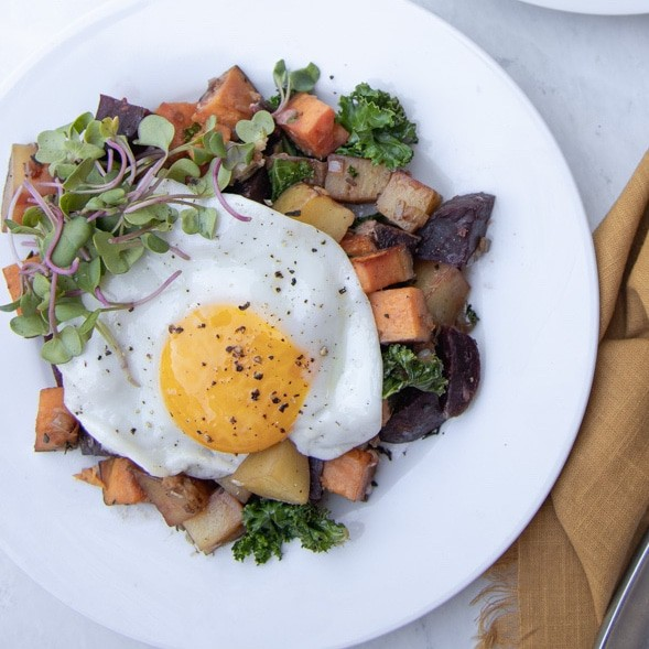 plate with root veggie hash and egg fried over easy on top.