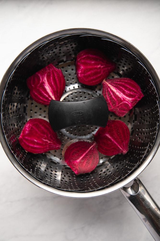 halved beets in a steamer basket