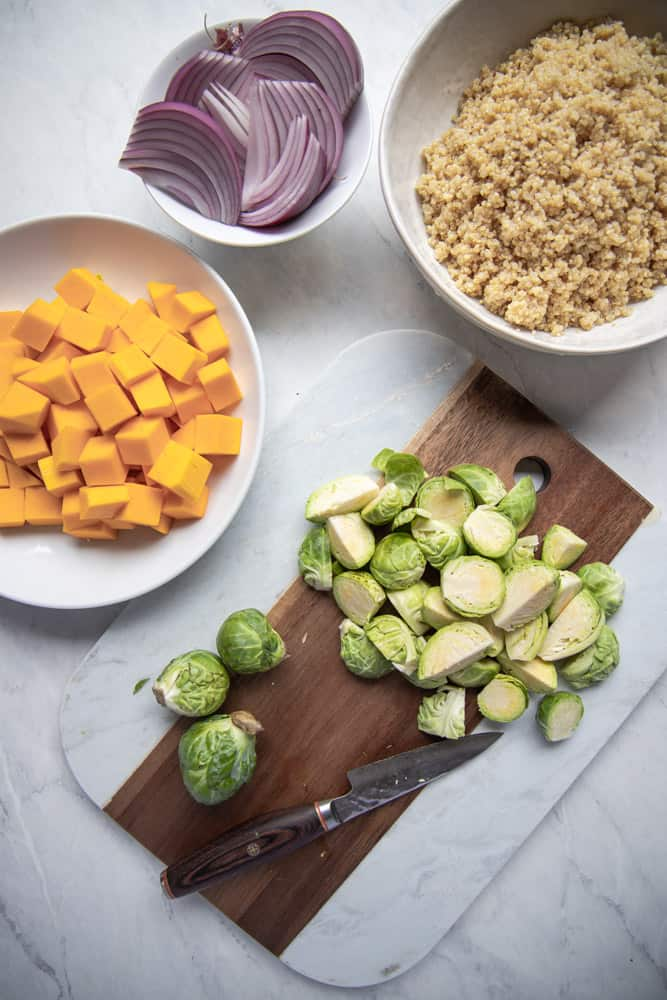 ingredients for nourish bowl prepped, with Brussel sprouts on a cutting board