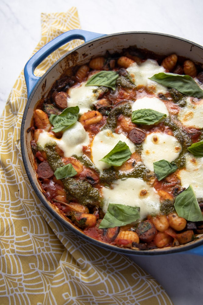 blue skillet with baked gnocchi and melted mozzarella on top garnished with basil leaves.