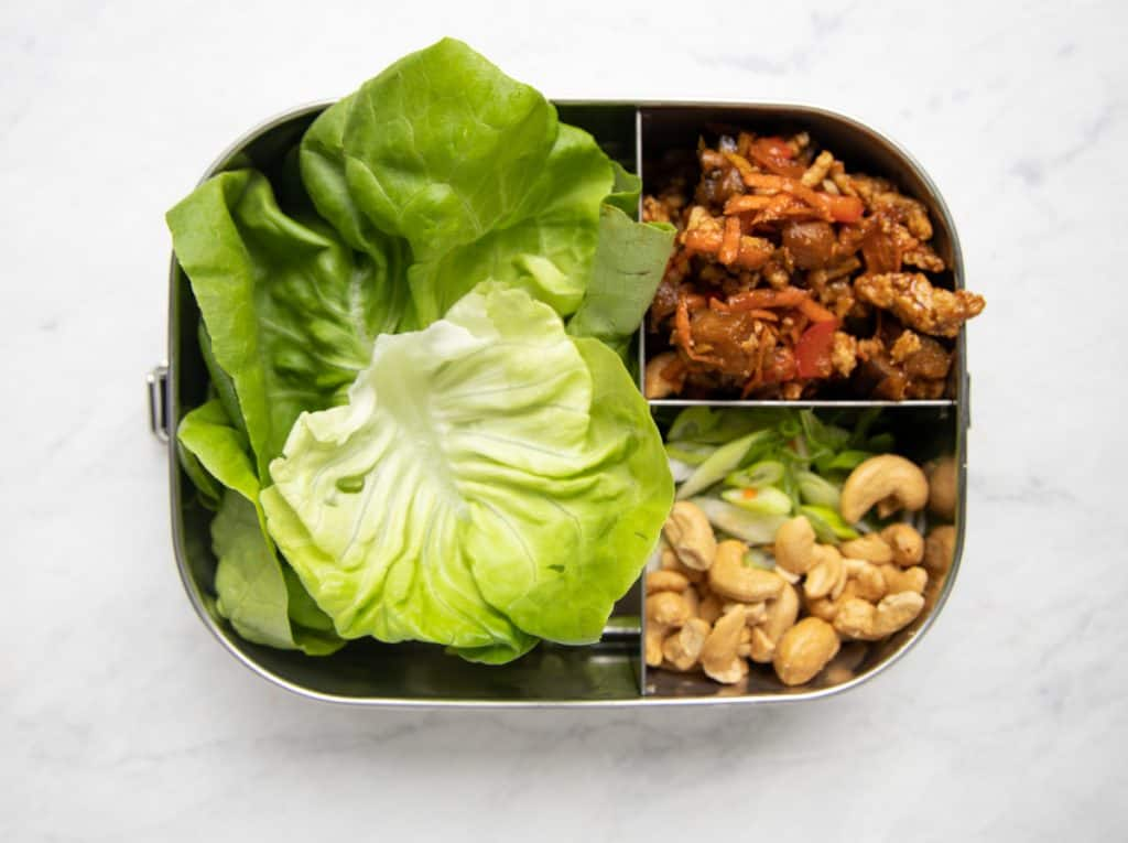 three compartment metal meal prep container with lettuce leaves, chicken mixture and cashews