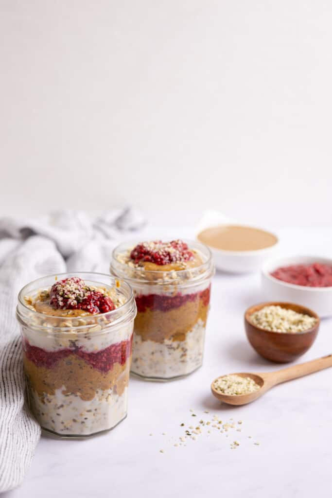 quinoa overnight oats in jars with ingredients in bowl