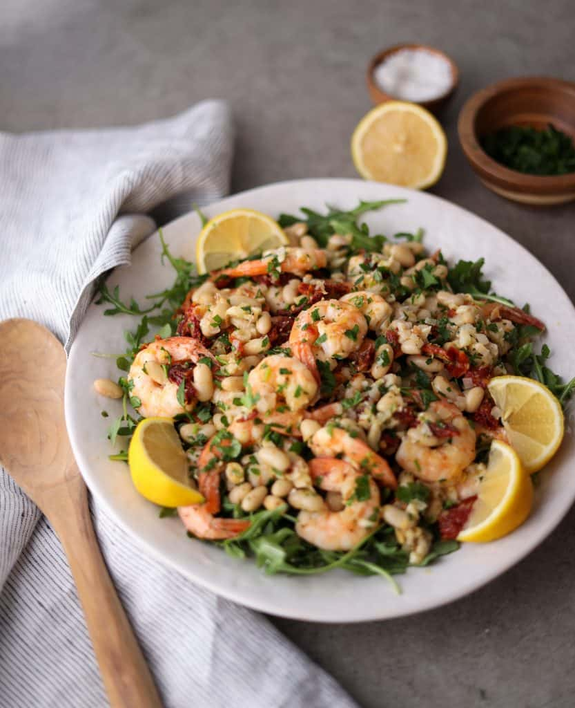 mediterranean shrimp salad on a platter with lemon wedges