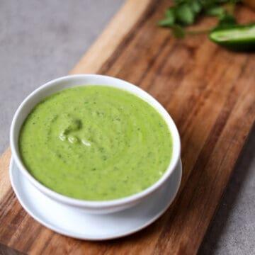bowl of cilantro jalapeño sauce on wood cutting board