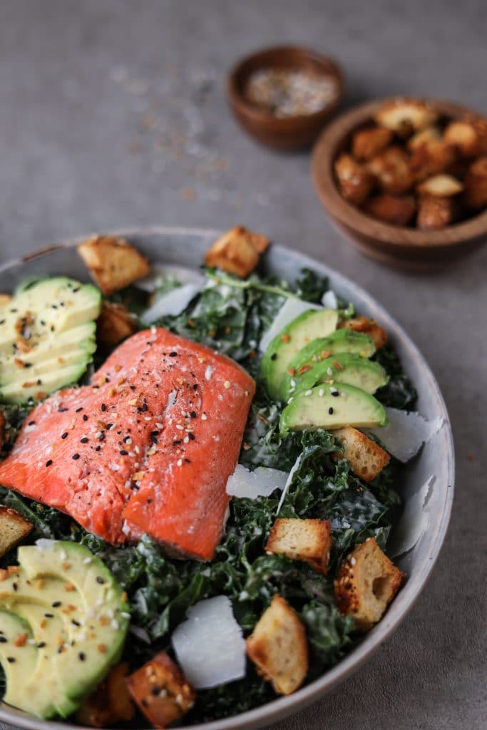 Close up of bowl of kale caesar with salmon.