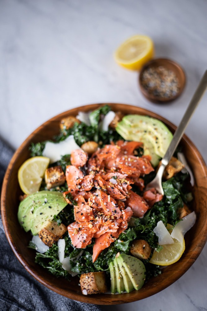 Close up of bowl of kale Caesar salad with flaked salmon over the top
