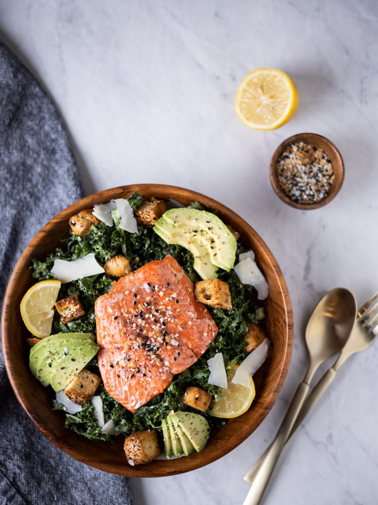 overhead photo of kale Caesar salad with salmon filet on top