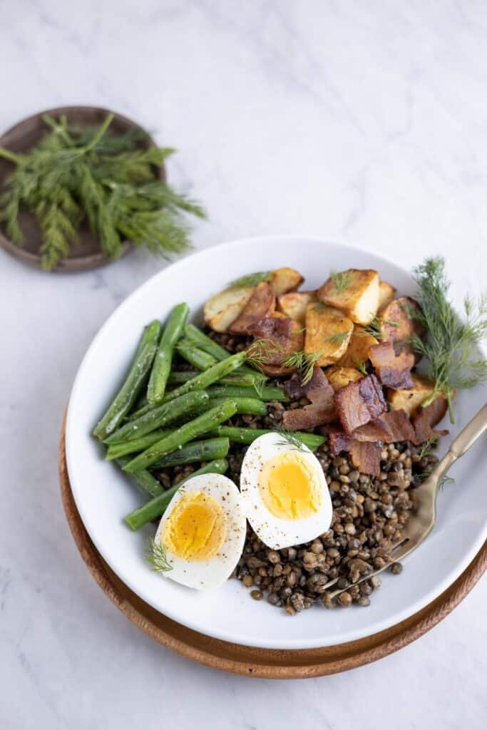 bowl of lentils with roasted potatoes, green beans and hardboiled eggs