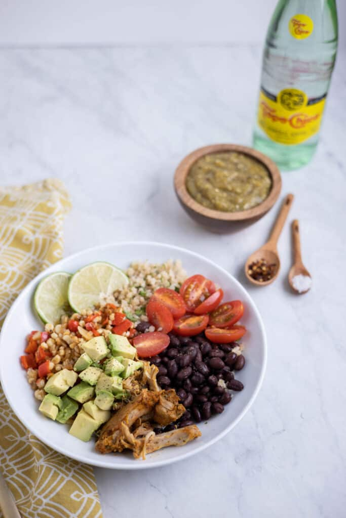 bowl of cauliflower rice topped with black beans, avocado and tomato