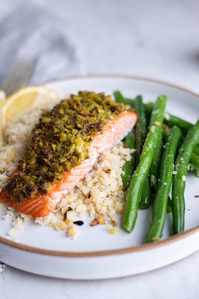 plate of cauliflower rice topped with pistachio crusted salmon filet and a side of green beans