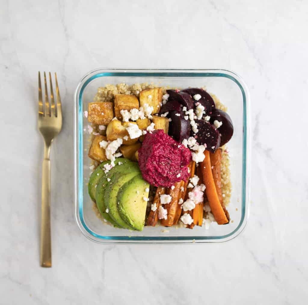 meal prep container of quinoa, carrots, tofu, beets and beet hummus topped with feta