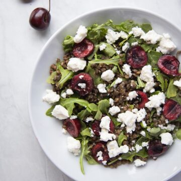 closeup image of bowl filled with cherry lentil salad topped with goat cheese