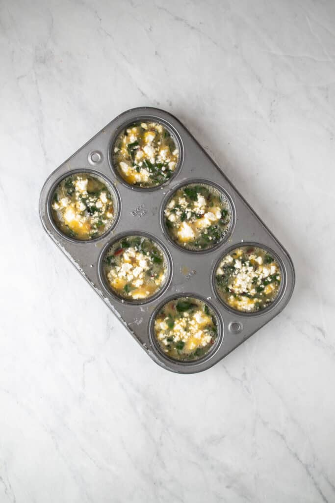 uncooked egg bites in a metal muffin tin