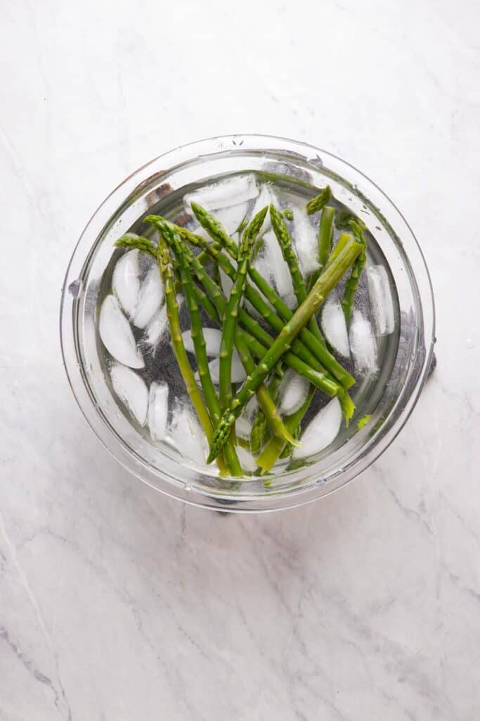 blanched asparagus spears in a bowl of ice water