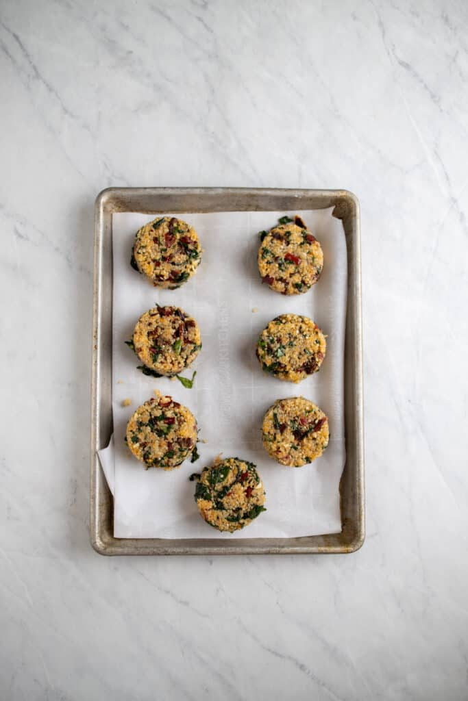 prepped raw sundried tomato and Swiss chard quinoa cakes on a cookie sheet