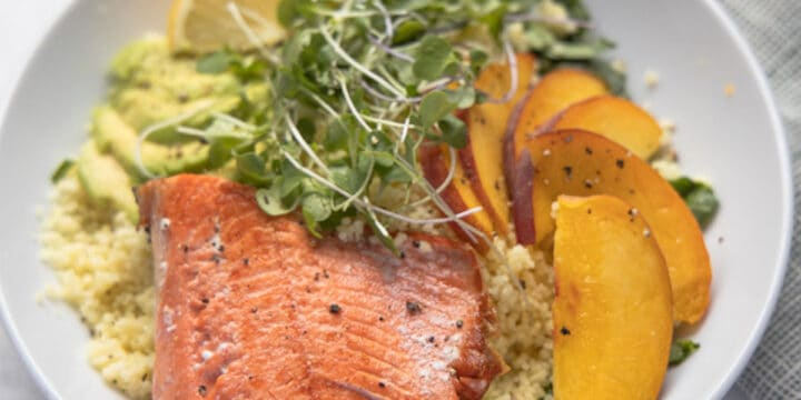close up image of bowl of quinoa topped with salmon filet, sliced peaches and micro greens