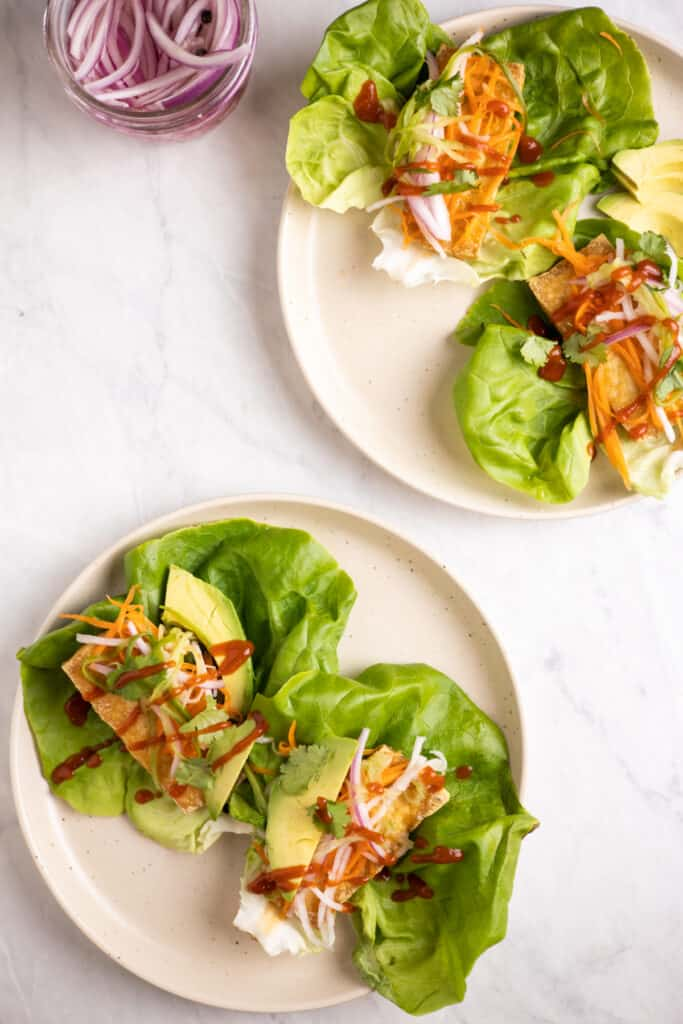 lettuce leaves on a plate filled with crispy tofu, pickled veggies, avocado and drizzled with sriracha