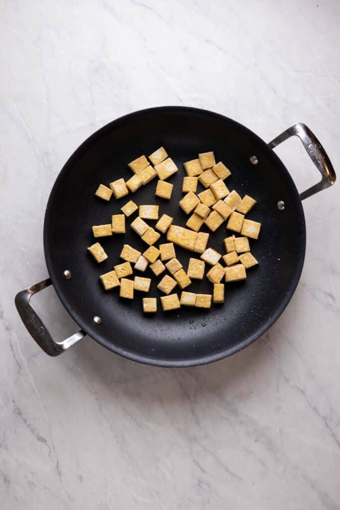 crispy tofu cubes in a skillet