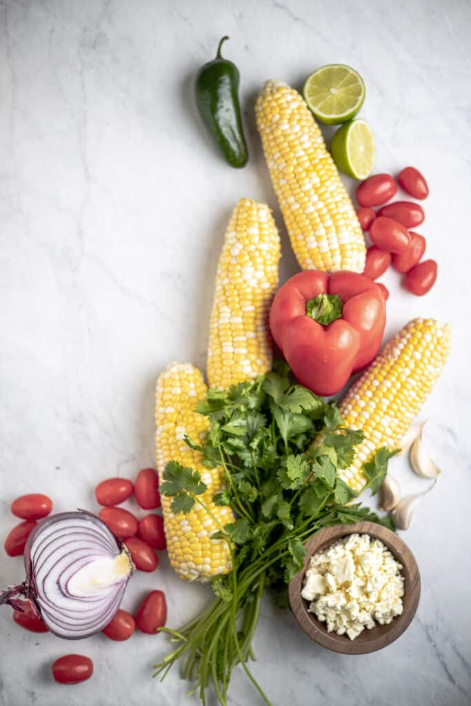 all of the ingredients for corn salad laid out onto a table