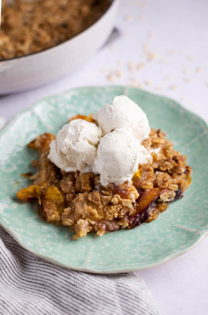 nectarine crumble on a plate with scoops of vanilla ice cream on top