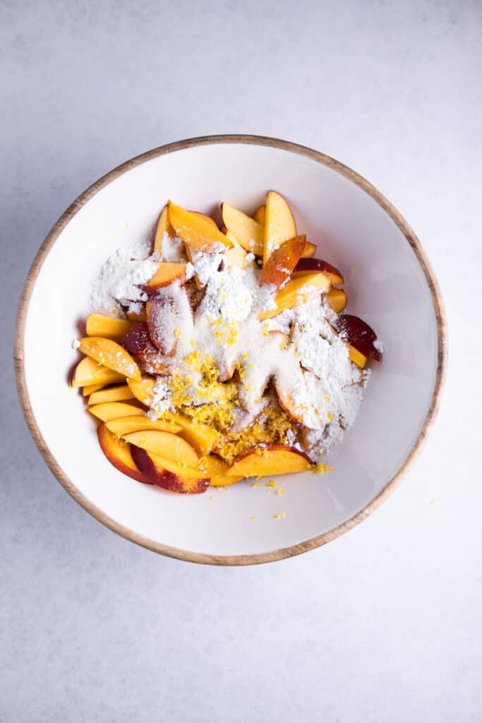 sliced nectarines, cornstarch and lemon zest in a bowl