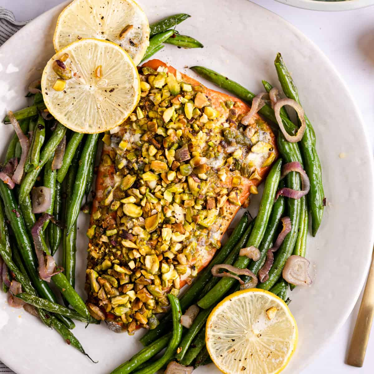 overhead photo of salmon crusted with pistachio and roasted green beans