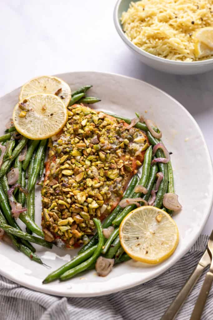 pistachio crusted salmon filet on a platter with green beans