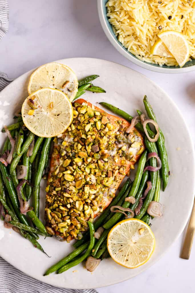 Salmon with pistachio crust on a platter with green beans