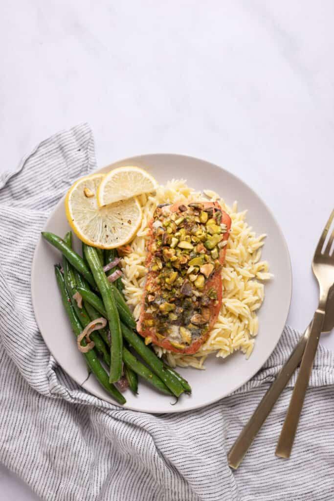 pistachio crusted salmon on a bed of orzo with green beans