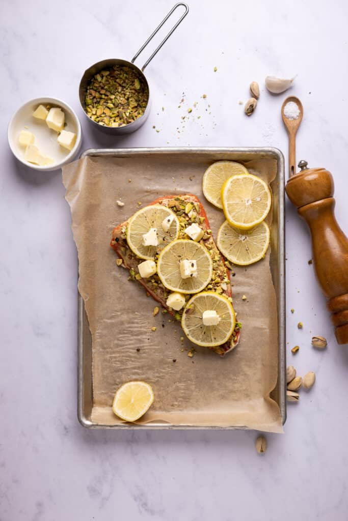 salmon topped with pistachios and lemon slices on a sheet pan