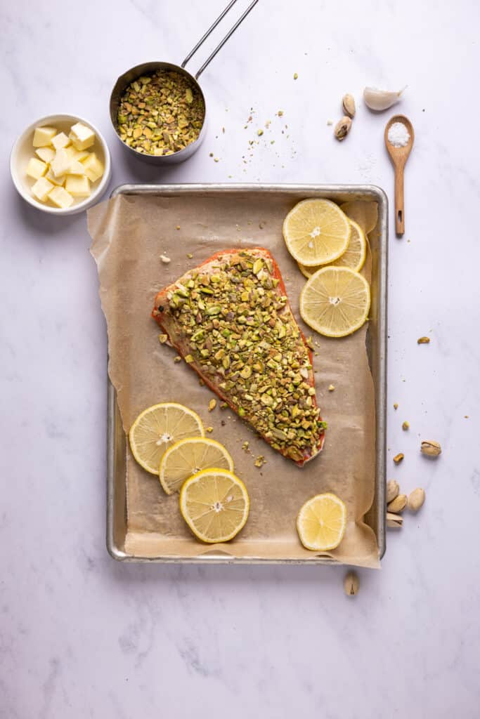 salmon topped with crushed pistachios on a sheet pan